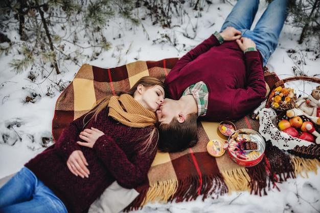 Мужчина и девушка лежат на одеяле на зимнем пикнике в день святого валентина в заснеженном парке. рождественский праздник, праздник. вид сверху, плоская планировка. Premium Фотографии