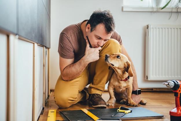 男と彼の犬が自宅で改修作業を行う Premium写真