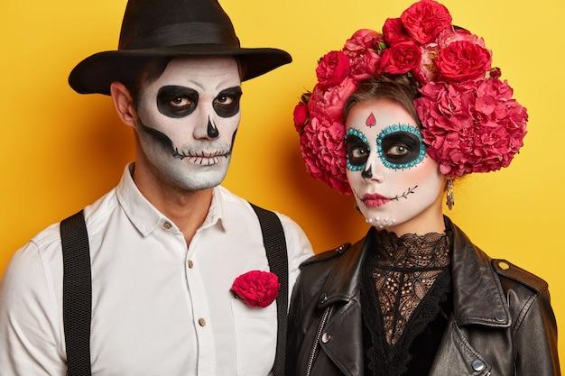 男と女は、黄色の背景の上に分離された頭蓋骨の化粧、黒と白の服を着ています。真面目な吸血鬼が一緒にハロウィーンを祝う 無料写真