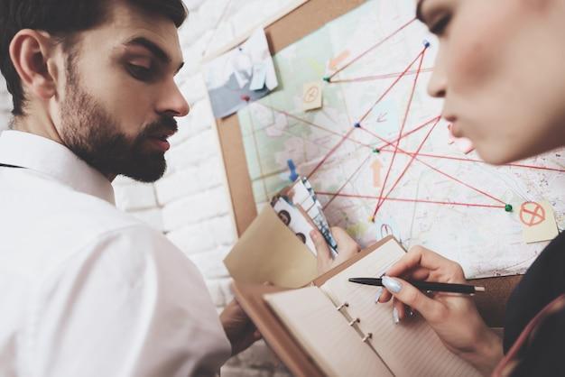 Мужчина и женщина смотрят на карту, обсуждают улики. Premium Фотографии