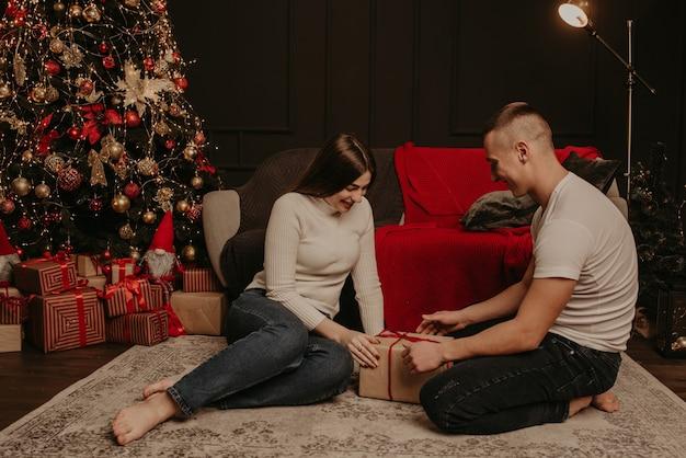 Влюбленная пара мужчина и женщина открывают подарочные коробки, развязывая бант возле елки Premium Фотографии