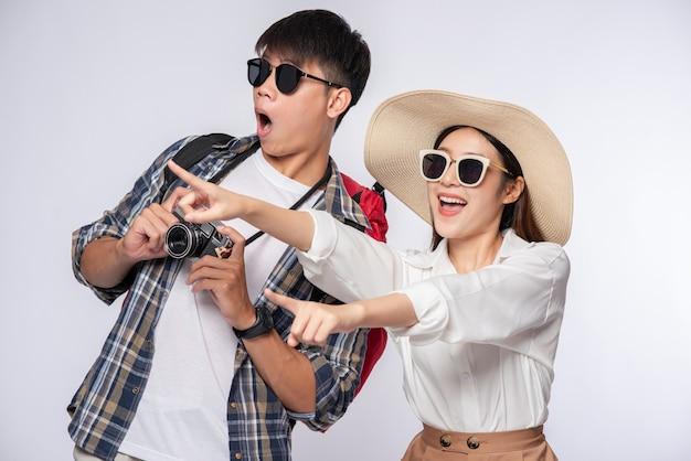 Мужчина и женщина одеты для путешествий, в очках и фотографируются Бесплатные Фотографии