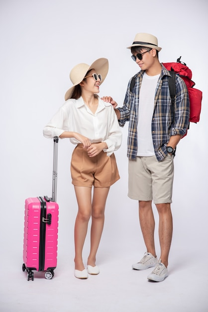 男と女はスーツケースを持って旅行するために眼鏡をかけてドレスアップ 無料写真