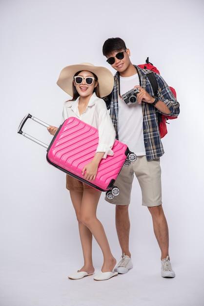 Мужчина и женщина, одетые в очки, путешествуют с чемоданами Бесплатные Фотографии