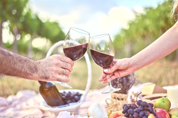 Мужчина и женщина руки с двумя бокалами винного тоста на пикнике на открытом воздухе Бесплатные Фотографии