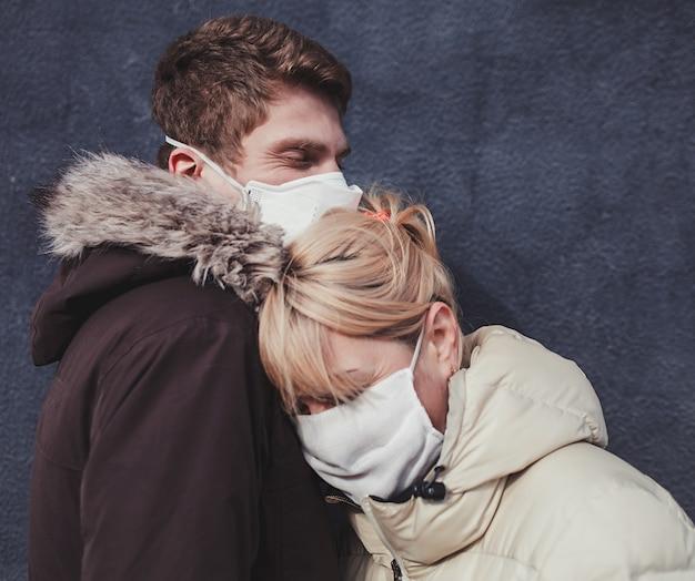 男と女の顔に医療用保護マスクを抱いて Premium写真