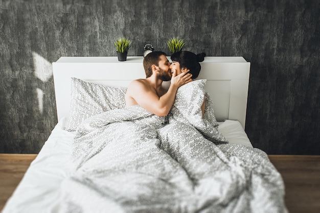 Мужчина и женщина в кровати занимаются фото