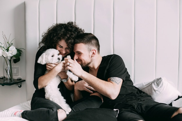 Man and woman in black play with little white dog on bed Free Photo