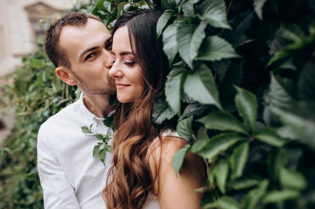Мужчина и женщина, целуя друг друга тендер, стоящий на улице в день своей свадьбы Бесплатные Фотографии