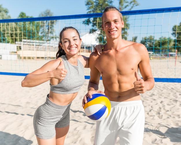 男と女がビーチバレーボールをプレイしながら親指でポーズ 無料写真