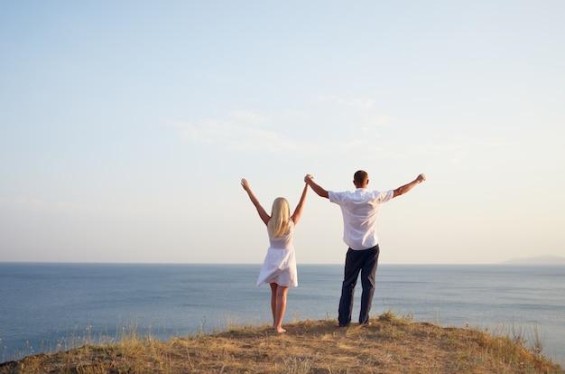 男と女はビーチに立っている間空に手を上げる Premium写真