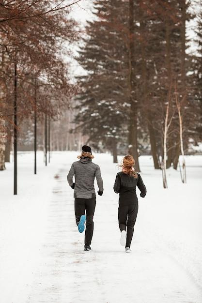 Мужчина и женщина, бегущие в лесу полный выстрел Premium Фотографии