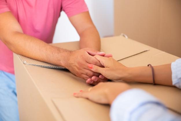 Мужчина и женщина поддерживают друг друга и держатся за картонную пачку при переезде в новую квартиру Бесплатные Фотографии