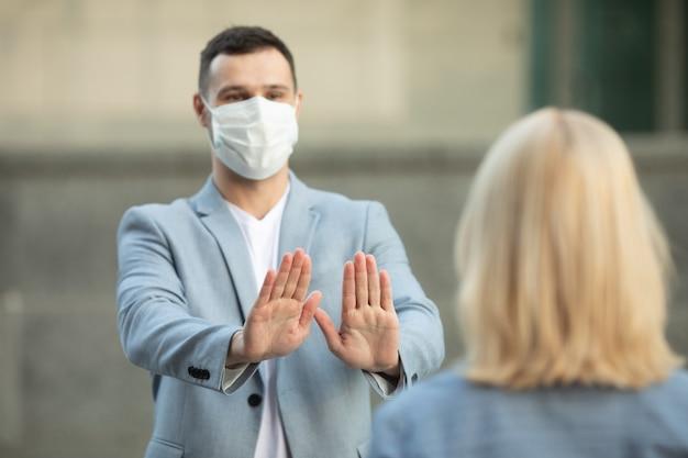 Мужчина и женщина в защитных масках стоят на расстоянии 2 м друг от друга, сохраняя социальное дистанцирование и избегая распространения коронавируса. Premium Фотографии