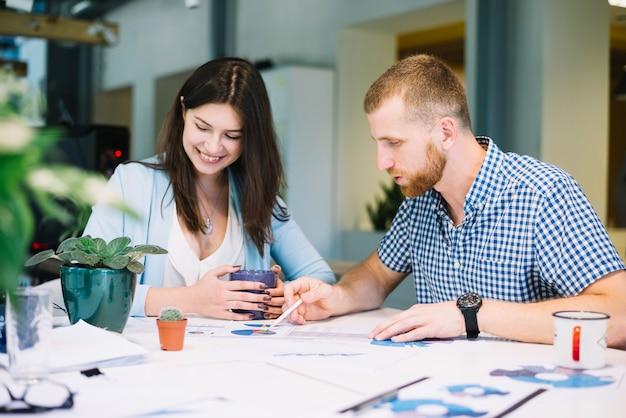 Мужчина и женщина, работающие на диаграммах вместе Бесплатные Фотографии