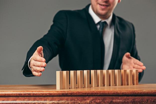 男とテーブルの上の木製キューブ。経営理念 無料写真