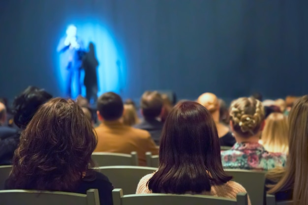 Man appears on stage in theater with many people Premium Photo