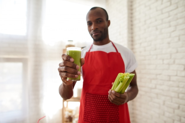 Man in apron holds glass of fresh celery juice at kitchen. Premium Photo