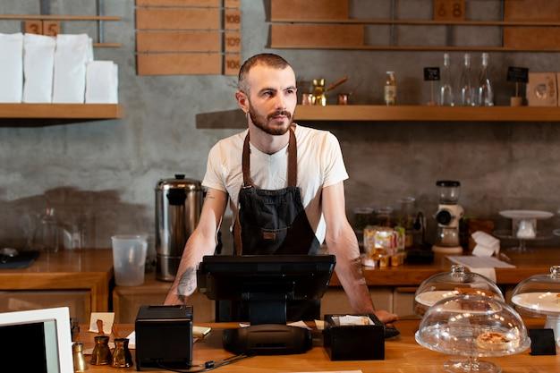 Man in apron posing at cash register Free Photo