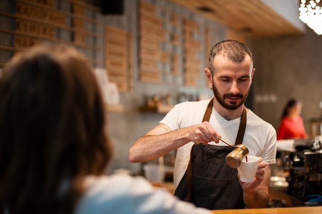 Man in apron pouring coffee in cup for customer Free Photo