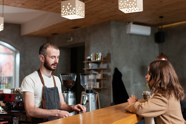 Man in apron preparing coffee for customer Free Photo