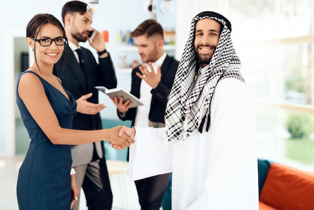 A man in arabian clothes and a girl are shaking hands. Premium Photo