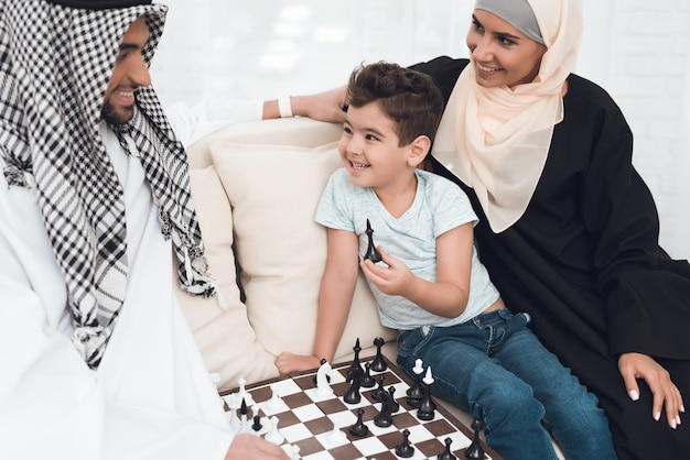 A man in arabic clothes plays chess with a little boy. Premium Photo