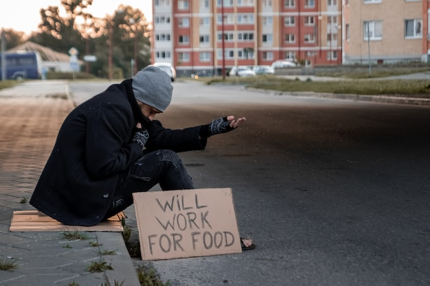 Man asks for alms on the street with a sign will work for food, homeless Premium Photo