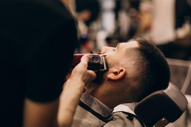 Мужчина в парикмахерской делает прическу и бороду Бесплатные Фотографии