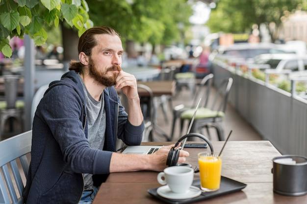 Человек на городской террасе работает с ноутбуком Бесплатные Фотографии