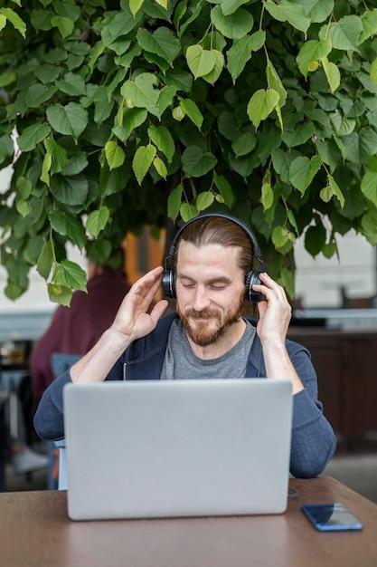 ノートパソコンとヘッドフォンで音楽を聴くテラスで男 無料写真
