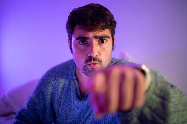 カメラに手のジェスチャーでアドバイスや注文を与えるベッドの男 Premium写真