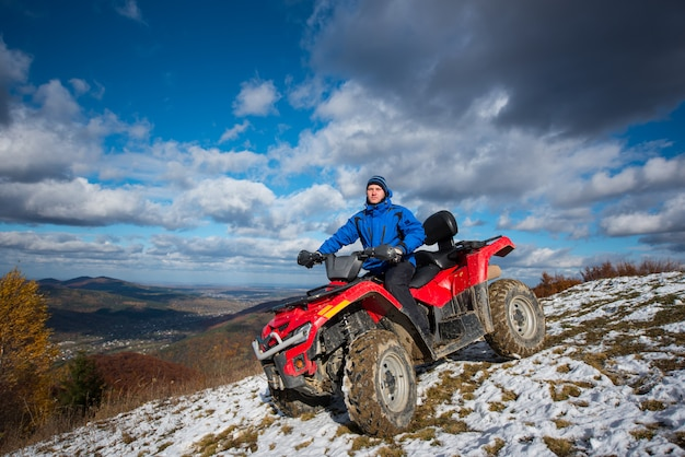 Man on atv riding down from the snow-capped peaks on a sunny day. Premium Photo