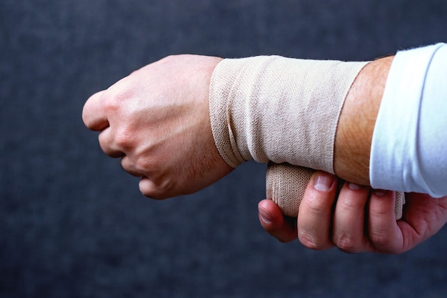 A man bandages his hand with a sports bandage Premium Photo