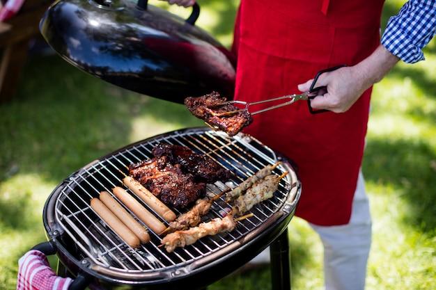 Мужчина готовит барбекю в парке Premium Фотографии