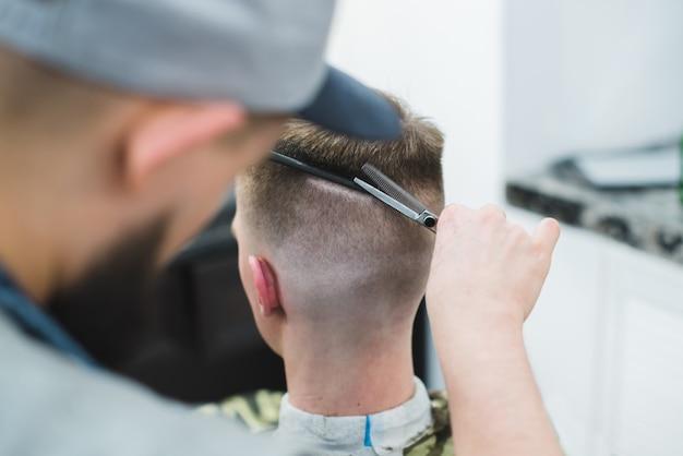 Мужской парикмахер создает стильную прическу для клиента. парикмахерские ножницы ее волосы с молодым человеком. Premium Фотографии