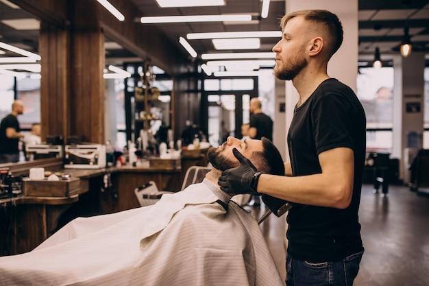 Man at a barbershop salon doing haircut and beard trim Free Photo