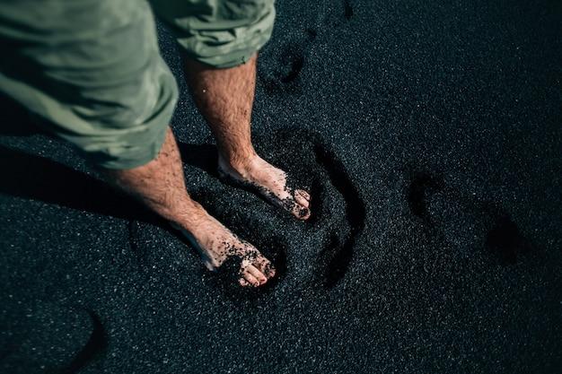 아이슬란드의 검은 모래 해변에 맨발로 남자 무료 사진