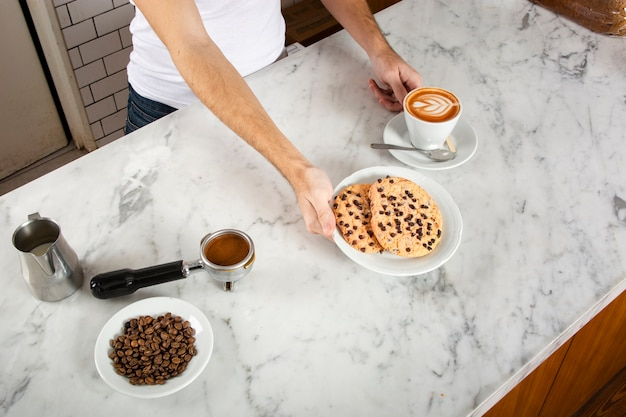 Man barista with cookies and a cappuccino Free Photo