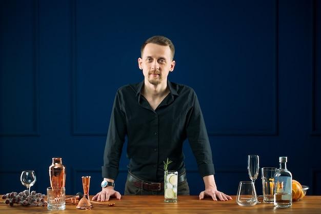 진 토닉으로 책상 뒤에 서있는 남자 바텐더 프리미엄 사진