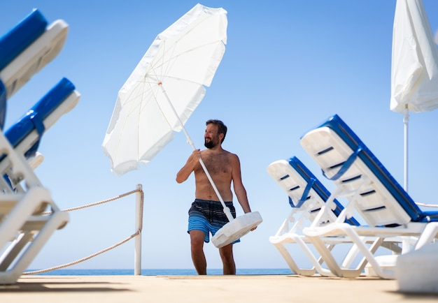 Man on beach jetty moving parasol Premium Photo
