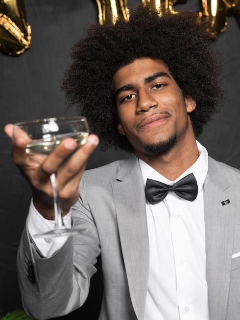Man in a beautiful party suit holding a glass of champagne Free Photo