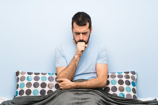 Man in bed is suffering with cough and feeling bad Premium Photo