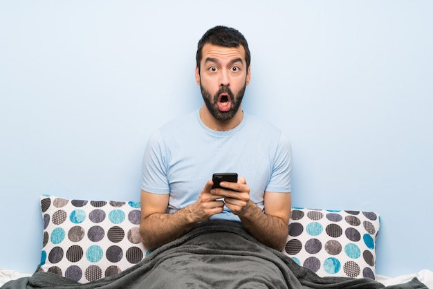 Premium Photo | Man in bed surprised and sending a message