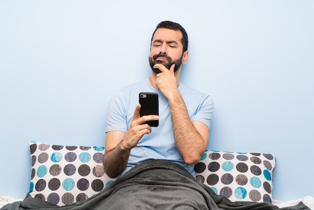Man in bed thinking and sending a message Premium Photo