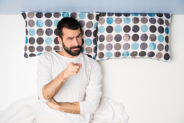 Man in bed in top view frustrated and pointing to the front Premium Photo