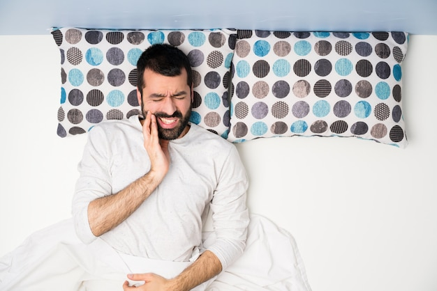 Man in bed in top view with toothache Premium Photo
