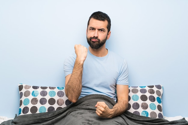 Man in bed with angry gesture Premium Photo