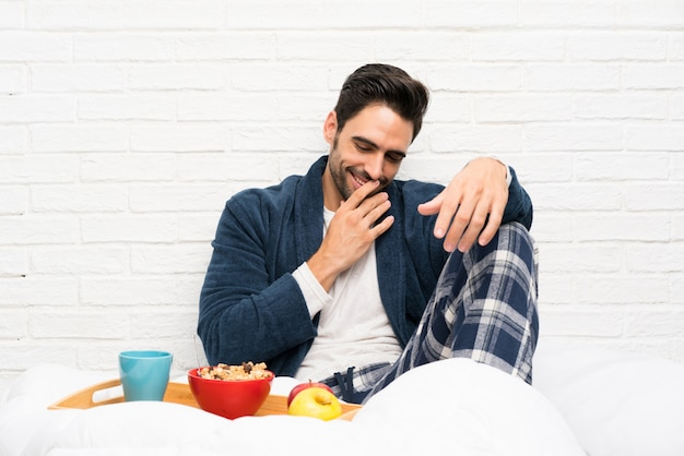 Man in bed with dressing gown and having breakfast smiling a lot Premium Photo