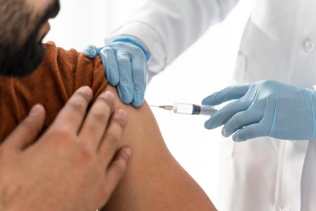 医者のクローズアップで予防接種を受けている男性 無料写真